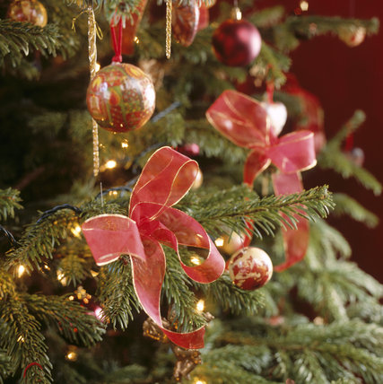 Close view of some of the decorations on a Christmas tree at Waddesdon Manor showing gilt-edged red ribbon bows, gold 'icicles' and red, green and gold glass baubles