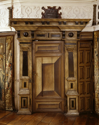 Close-up of the doorcase (1593), trompe l'oeil door and early 17th century painted wainscot, in the Long Gallery at Powis Castle