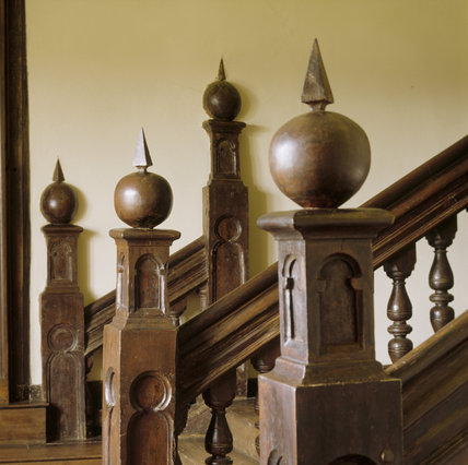 A partial view from the upper landing of the staircase showing the oak newel posts surmounted by grenades