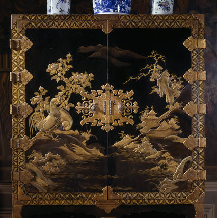 Detail of the 17th-century Japanese lacquer cabinet decorated with landscapes in gold on the black front in the Grand Staircase at Petworth