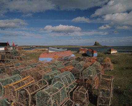 View of Lindisfarne Castle with crabpots and fishing boats in the foreground