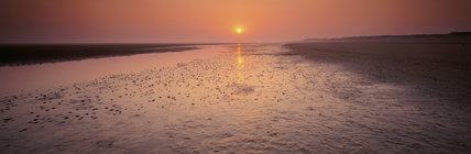 A sunrise view across the beach looking towards Brancaster Harbour