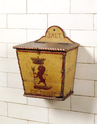 The salt dispenser hanging on the Kitchen Wall. A wooden box with a symbol of a lion painted on it.