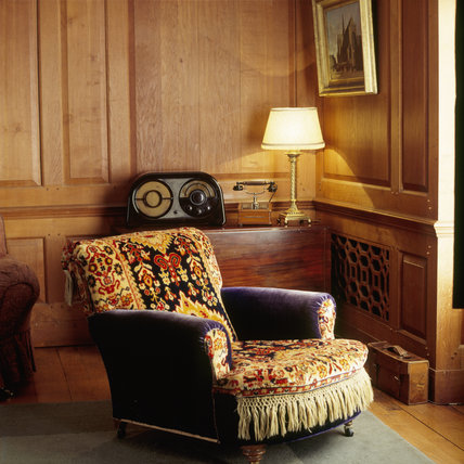 Corner view of the Boudoir at Castle Drogo showing an original telephone, electric table lamp, radio, comfortable armchair and latticed radiator