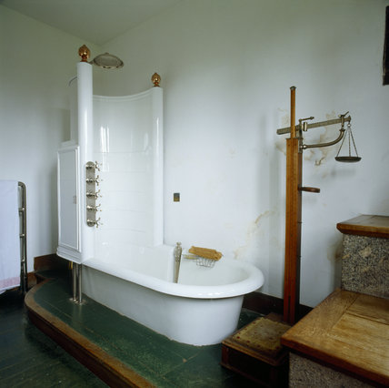 The Bathroom showing the bath complete with shower compartment and old style weighing scales