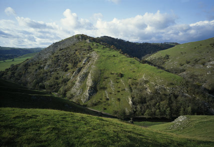 From the summit of Thorpe Cloud, Dovedale appears, protected by the limestone crags of Bunster Hill