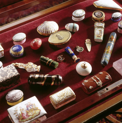 A close-up of a collection of pill boxes in a display case in the Drawing Room at Polesden Lacey