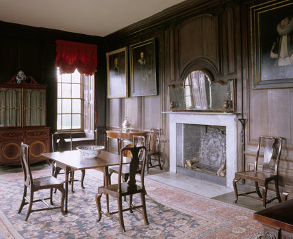 The Dining Room at Canons Ashby including the chimney-piece, walnut-framed mirror, dining table and secretaire bookcase