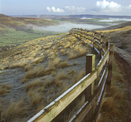 This fence marks the edge of the NT's property in Mam Tor, Edale is visible to the left and in the distance NT moorland rising above the reservoirs