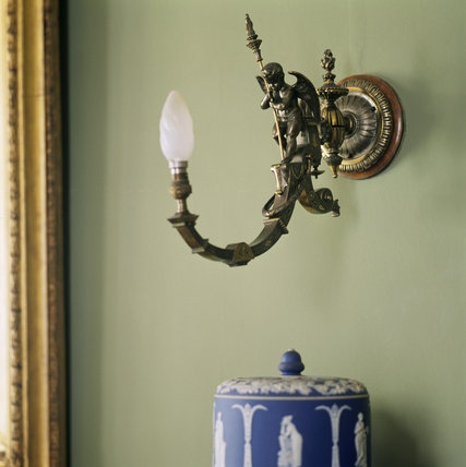 Detail of an electric light fitting featuring a cherub holding a torch, in the Dining Room at Sunnycroft