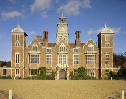 The south front of Blickling Hall showing the clock tower under a blue sky
