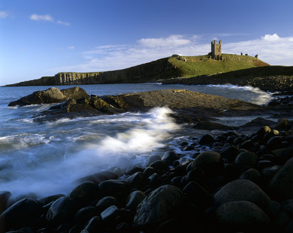 The derelict Dunstanburgh Castle standing out against the sky, viewed from the boulder strewn Embleton Bay