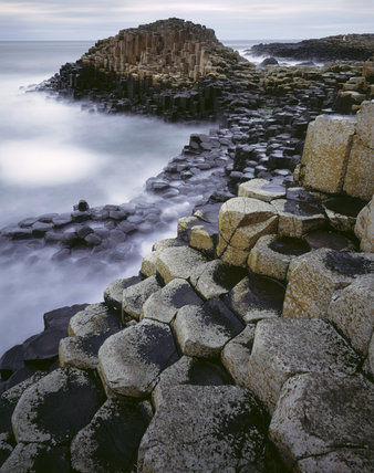 A view of the unusual rock formations at Giant's Causeway, taken under a dark forboding sky and with a blur of crashing waves