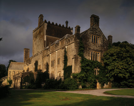 An oblique view of Buckland Abbey, viewed from the south east, lit by a setting sun