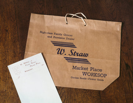Close-up of brown paper carrier bag with the inscription: `High-class Family Grocer and Provision Dealer, W