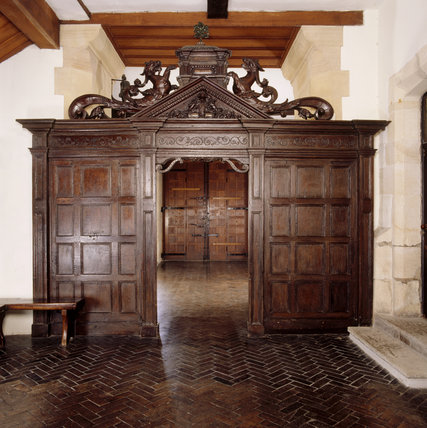The oak panelled screen with triangular pediment including an escutcheon of the Strickland family arms