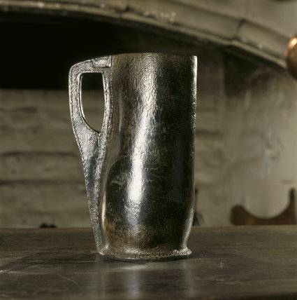 A close-up detail of a black jack leather tankard coated with tar or pitch on a table in the Kitchen at East Riddlesden Hall