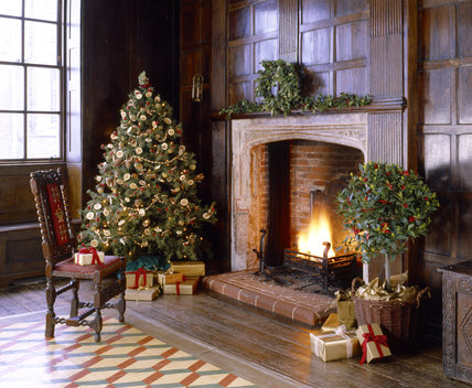 A delightful traditional christmas scene at Sutton House showing a beautifully decorated tree, gifts and open log fire