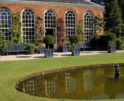 View across the pond of the 18th century Orangery with roses 'fellenberg', 'alister stella gray' and 'desprez a fleur jaunes' growing against the red brick walls