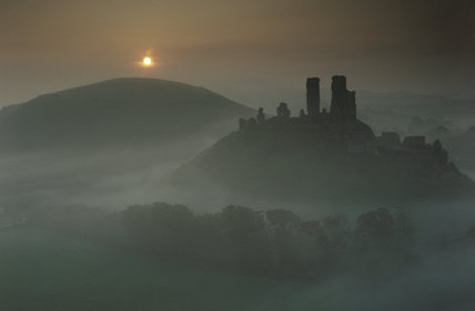 The sun rising behind the ruins of Corfe Castle in a misty dawn, viewed from West Hill