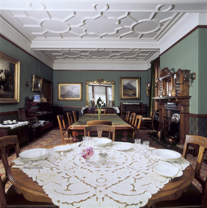 The Dining Room at Sunnycroft, showing the dining table, fire- place, mirror and display cabinet containing china