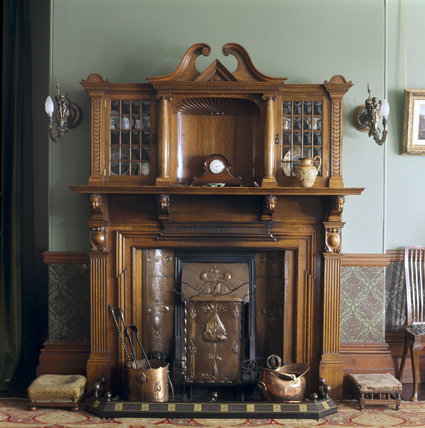 Close-up of the Dining Room wooden fireplace at Sunnycroft, with glass display cabinets and clock