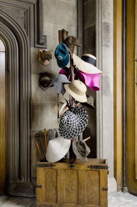 The hat stand adorned with a range of headgear and a chest with walking sticks, in the Front Hall at Coughton Court, Warwickshire