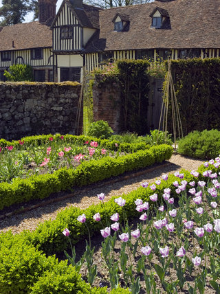 The Cutting Garden at Ightham Mote, Sevenoaks, Kent, a fourteenth-century moated manor house with the cottages in the background