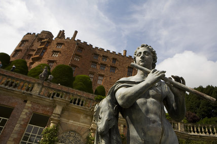 Close view of an C18th lead statue of a shepherd by John Van Nost with the castle rearing up behind at Powis Castle & Garden, Welshpool, Powys, Wales