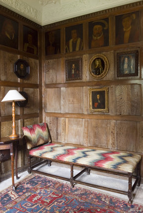 Corner of the King's Room showing the flame-stitch day bed and panelled walls with portraits of the Kings and Queens of England, at Westwood Manor, near Bradford-on-Avon, Wiltshire