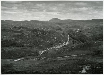 Photograph of a winding road in a rocky landscape. A mountain can be seen on the horizon.