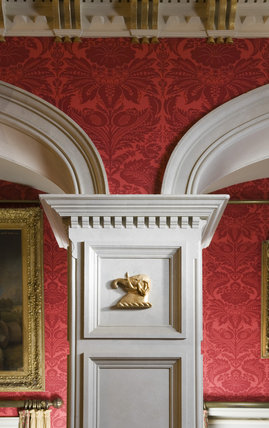 Detail of the arch and cornice with red flock wallpaper in the Saloon at Coughton Court, Warwickshire