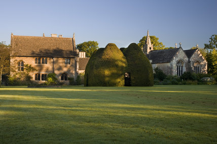 View over the large lawn at the fifteenth-century Great Chalfield Manor, Wiltshire, towards the yew house which was planted in the early 1900s to mark the restoration of the house beyond