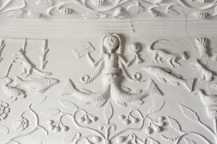 A mermaid, fish and other animals depicted in the Jacobean plasterwork overmantle of the Kings Room at Westwood Manor, near Bradford-on-Avon, Wiltshire