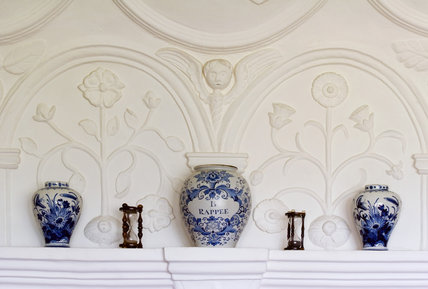 Blue and white ceramics on display against the plasterwork overmantle of the Music Room at Westwood Manor, near Bradford-on-Avon, Wiltshire