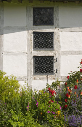 Close view of three diamond-paned windows at Lower Brockhampton House, the medieval manor house on the Brockhampton Estate in Worcestershire