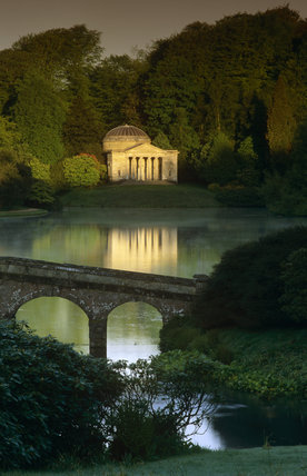 The Pantheon reflected in the lake at Stourhead, Wiltshire with the Palladian bridge in the foreground