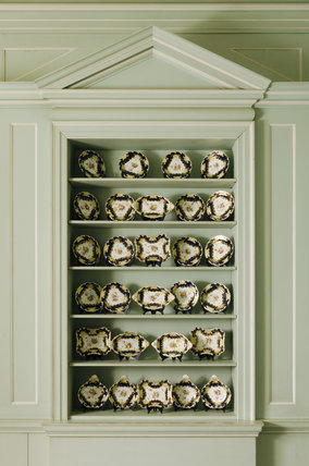 Display shelves containing an 1825 Coalport dessert service in the Green Library at Mottisfont Abbey, Hampshire