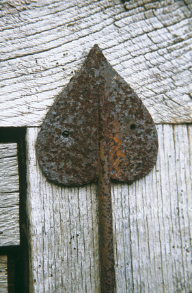 An Arts and Crafts style metal hinge on a wooden door at Tyntesfield, North Somerset