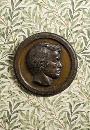 Bronze bas-relief plaque of Thomas Carlyle by Thomas Woolner, 1855, against the William Morris wallpaper