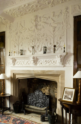 The Kings Room at Westwood Manor, near Bradford-on-Avon, Wiltshire, with Jacobean plasterwork on the ceiling and fireplace, a flame-stitch day bed and panelled walls with paintings of the Kings and Queens of England
