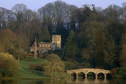 The Bristol High Cross, St Peter's Church and the Palladian Bridge in winter at Stourhead, Wiltshire