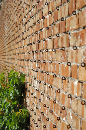 The brick wall with the metal loops used for holding wire supports in the Kitchen Garden at Tyntesfield, Wraxall, North Somerset
