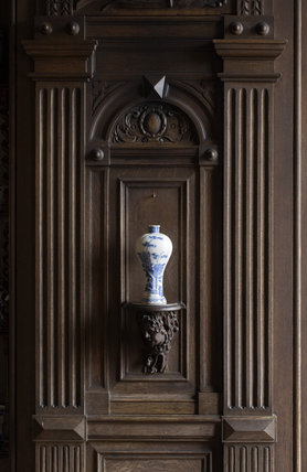 Blue and white ceramic vase on a wooden bracket in the wood panelled Garden Hall in the new house at Scotney Castle, Kent