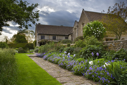 A beautiful blue and white border with hardy geraniums and irises in the garden at the fifteenth-century Great Chalfield Manor, Wiltshire