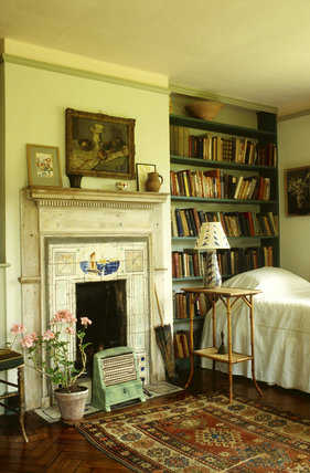 Monk's House, view towards the fireplace in Virginia Woolfs bedroom, showing an electric fire, bookcase and lamp