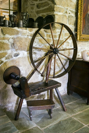 A spinning wheel on the green slate flagged floor in the Hall at Plas yn Rhiw, Pwllheli, Gwynedd