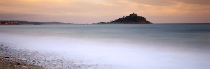 Panoramic view of St.Michael's Mount at dawn with sunlight on the west side of the castle, the houses below it and those to the east. Misty sunshine also illuminates the surrounding sea.