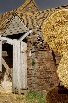 A dilapidated building with two hay barrels in the foreground at the Mose House Farm on the Dudmaston Estate demonstrating the repair work that is needed to be done