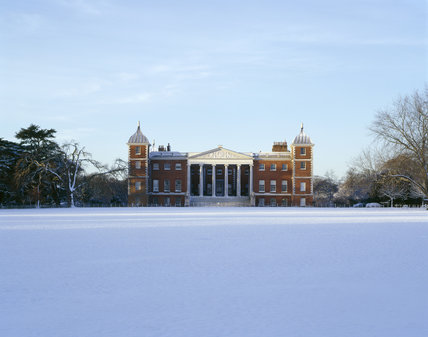 The East front of Osterley Park, reconstructed by Robert Adam in 1760s, seen over a snowy lawn showing figured pediment, Corinthian columns, balustrade and snow-covered terrace